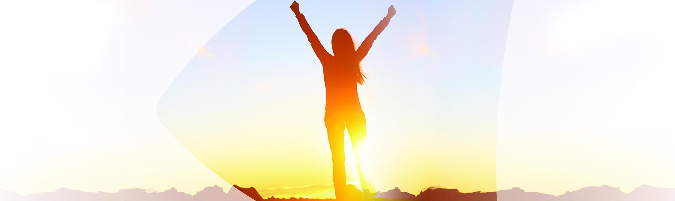Femme au coucher du soleil avec ses bras ouverts