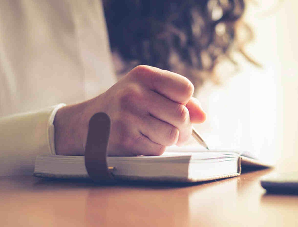 Femme écrivant sur son bloc-notes