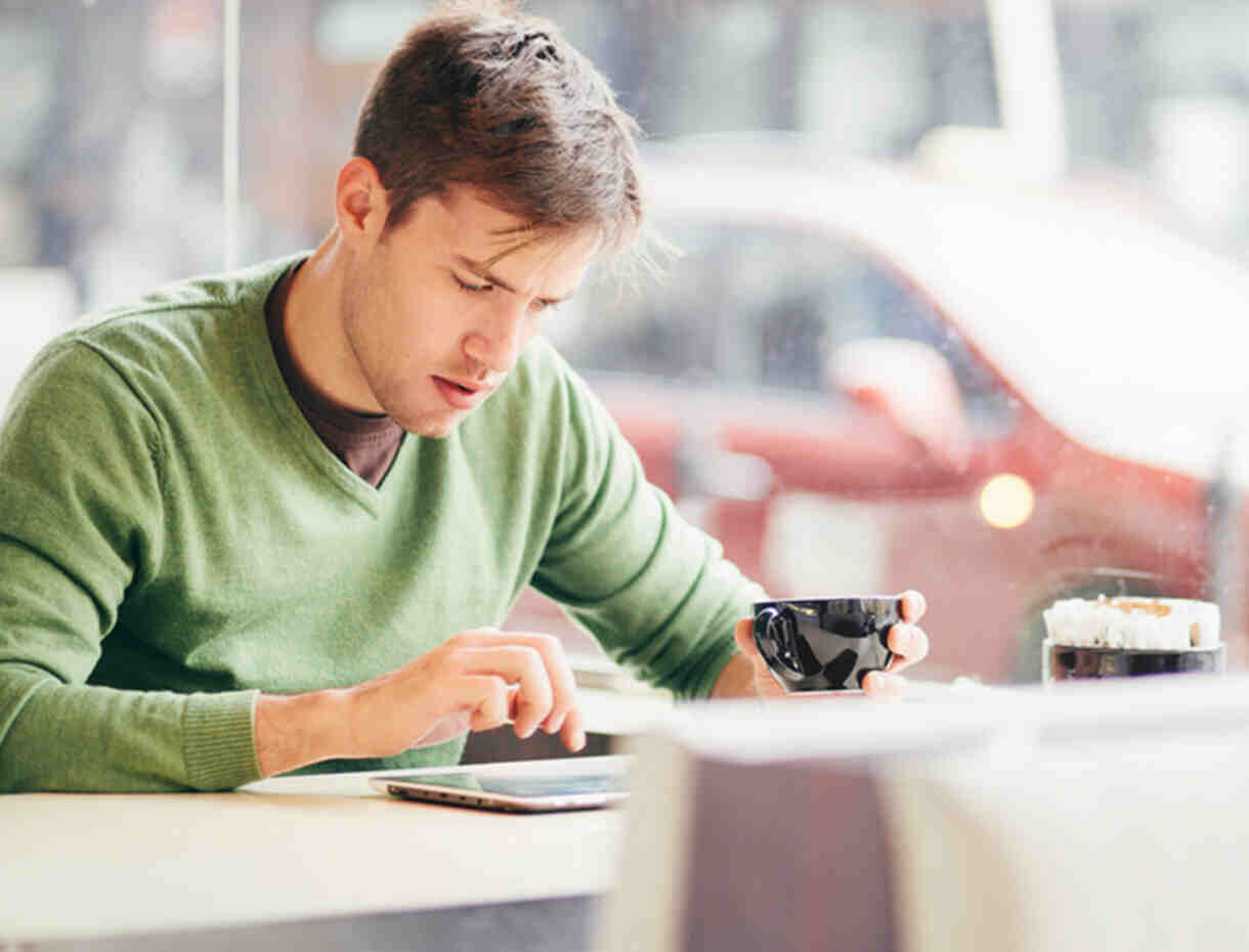 L'homme utilisant sa tablette alors qu'il boit du café